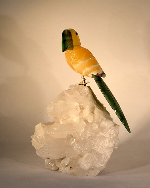 Yellow bird with dark green beak and feather perched on transparent quartz