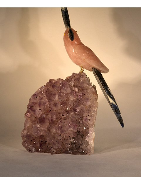 Carved Rose Quartz Bird with green tail and beak on amethyst stone