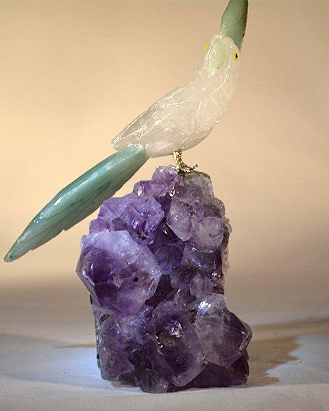 Crystal Bird on purple quartz looks away to the side