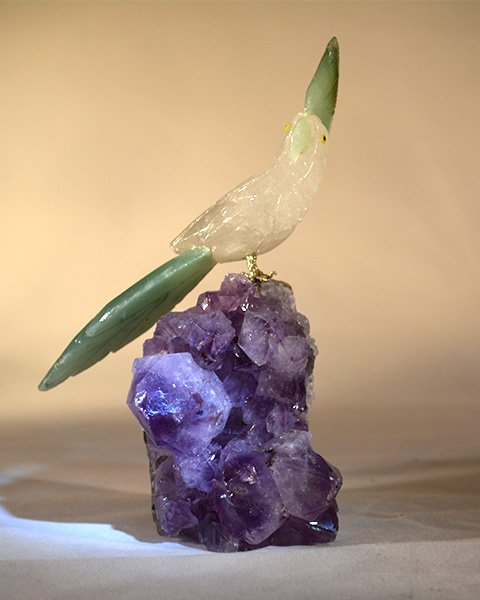 Crystal Cockatoo with green tail feather and head perched on amethyst stone