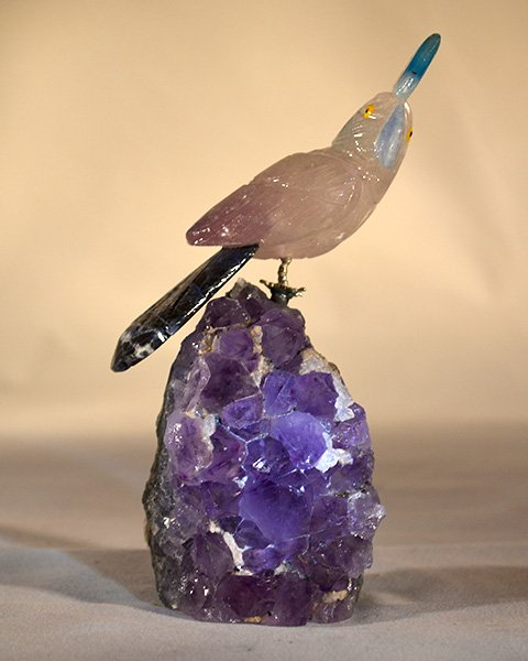 Rose quartz cockatoo with dark tail feather perched on amethyst stone