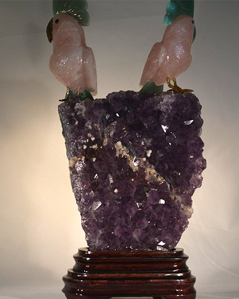 Two rose quartz love birds perched on amethyst stone looking in opposite direction