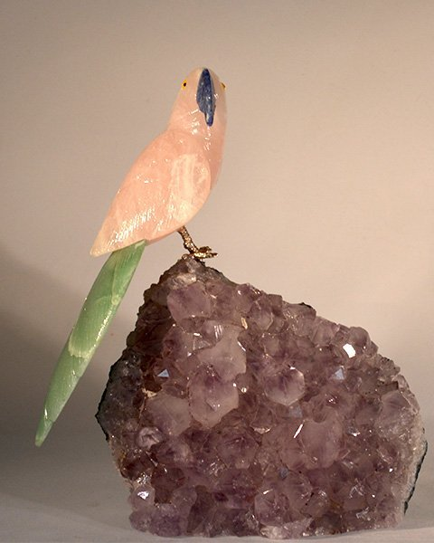 rose gemstone parrot with green tail on amethyst rock
